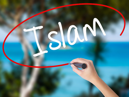 Woman Hand Writing Islam with black marker on visual screen. Isolated on nature. Business concept. Stock Photo