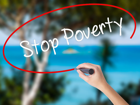 eradication: Woman Hand Writing Stop Poverty  with black marker on visual screen. Isolated on nature. Business concept. Stock Photo