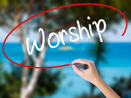 Woman Hand Writing Worship with black marker on visual screen. Isolated on nature. Business concept. Stock Photo