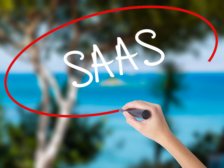 Woman Hand Writing SAAS with black marker on visual screen. Isolated on nature. Business concept. Stock Photo