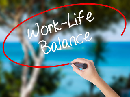 Woman Hand Writing Work-Life Balance with black marker on visual screen. Isolated on nature. Business concept. Stock Photo
