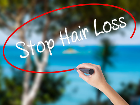 calvicie: Woman Hand Writing Stop Hair Loss  with black marker on visual screen. Isolated on nature. Business concept. Stock Photo