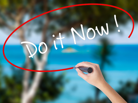 Woman Hand Writing Do it Now with black marker on visual screen. Isolated on nature. Business concept. Stock Photo Stock Photo