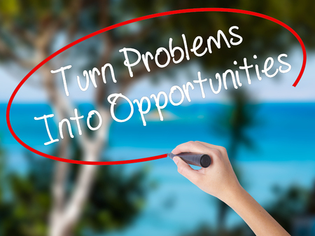 Woman Hand Writing Turn Problems into Opportunities with black marker on visual screen. Isolated on nature. Business concept. Stock Photo Stock Photo