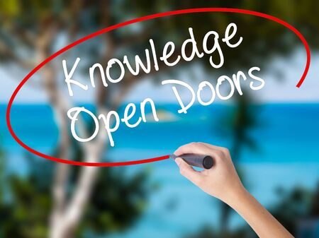 Woman Hand Writing  Knowledge Open Doors  with black marker on visual screen. Isolated on nature. Business concept. Stock Photo