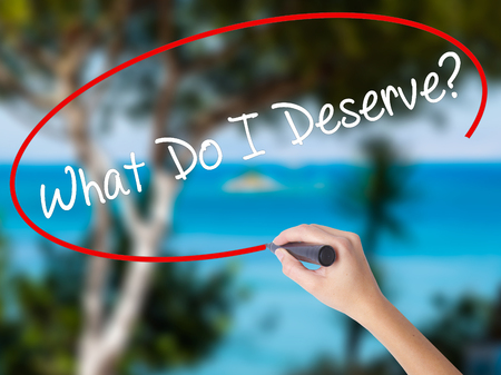 Woman Hand Writing What Do I Deserve? with black marker on visual screen. Isolated on nature. Business concept. Stock Photo