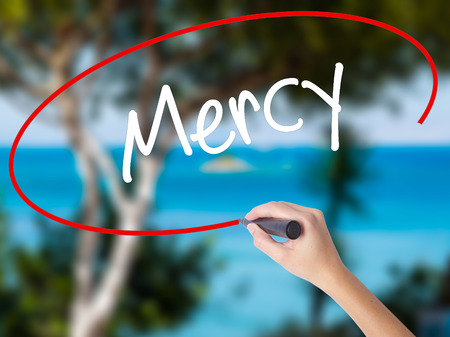Woman Hand Writing Mercy with black marker on visual screen. Isolated on nature. Business concept. Stock Photo