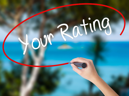 Woman Hand Writing Your Rating with black marker on visual screen. Isolated on nature. Business concept. Stock Photo