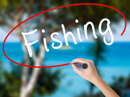 Woman Hand Writing Fishing with black marker on visual screen. Isolated on nature. Business concept. Stock Photo