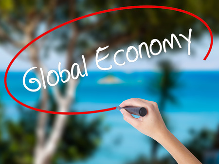 Woman Hand Writing Global Economy with black marker on visual screen. Isolated on nature. Business concept. Stock Photo