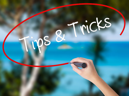 Woman Hand Writing Tips & Tricks with black marker on visual screen. Isolated on nature. Business concept. Stock Photo