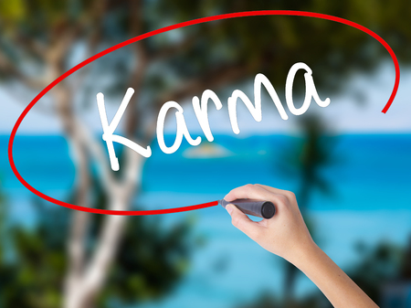 Woman Hand Writing Karma  with black marker on visual screen. Isolated on nature. Business concept. Stock Photo