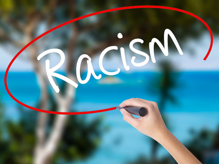 Woman Hand Writing Racism with black marker on visual screen. Isolated on nature. Business concept. Stock Photo Stock Photo