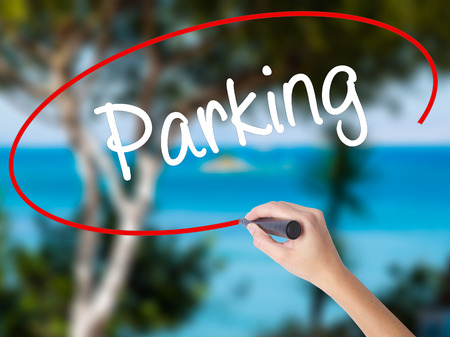 Woman Hand Writing Parking with black marker on visual screen. Isolated on nature. Business concept. Stock Photo