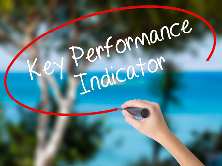 Woman Hand Writing Key Performance Indicator with black marker on visual screen. Isolated on nature. Business concept. Stock Photo