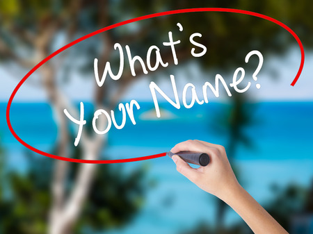 Woman Hand Writing Whats your Name? with black marker on visual screen. Isolated on nature. Business concept. Stock Photo