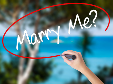 Woman Hand Writing Marry Me? with black marker on visual screen. Isolated on nature. Business concept. Stock  Photo