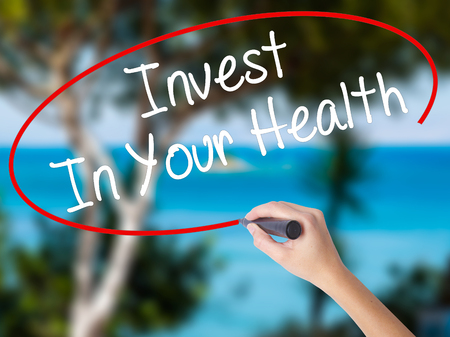 Woman Hand Writing Invest In Your Health with black marker on visual screen. Isolated on nature. Business concept. Stock Photo
