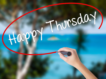 Woman Hand Writing Happy Thursday with black marker on visual screen. Isolated on nature. Business concept. Stock  Photo