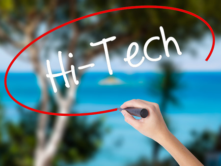 Woman Hand Writing Hi-Tech with black marker on visual screen. Isolated on nature. Business concept. Stock Photo