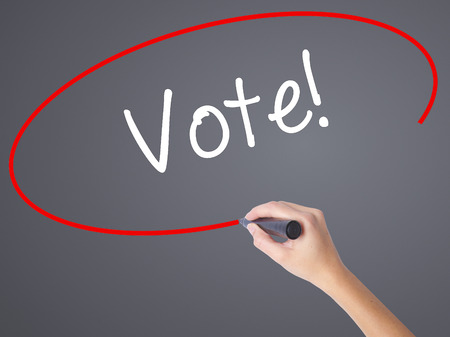 elect: Woman Hand Writing Vote! with black marker on visual screen. Isolated on grey. Business concept. Stock Photo