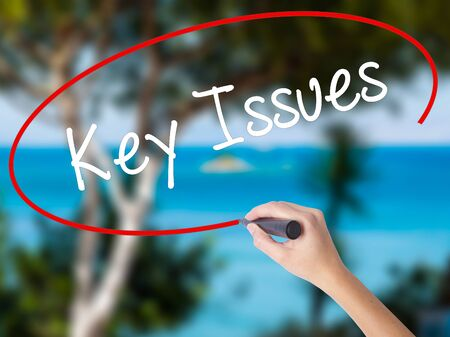 Woman Hand Writing Key Issues with black marker on visual screen. Isolated on nature. Business concept. Stock Photo Stock Photo