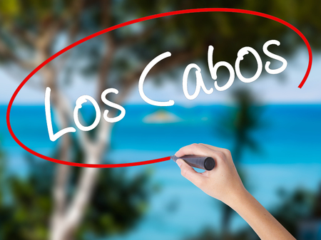 Woman Hand Writing Los Cabos with black marker on visual screen. Isolated on nature. Business concept. Stock Photo