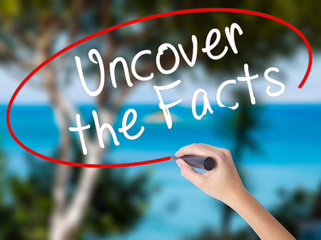 misleading: Woman Hand Writing Uncover the Facts with black marker on visual screen. Isolated on nature. Business concept. Stock Photo