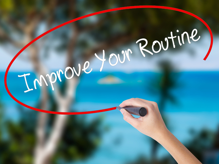 habitual: Woman Hand Writing Improve Your Routine with black marker on visual screen. Isolated on nature. Business concept. Stock Photo