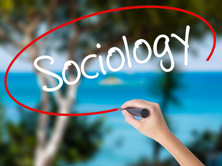 sociologia: Woman Hand Writing Sociology  with black marker on visual screen. Isolated on nature. Business concept. Stock Photo