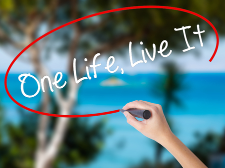 Woman Hand Writing One Life Live It with black marker on visual screen. Isolated on nature. Business concept. Stock Photo