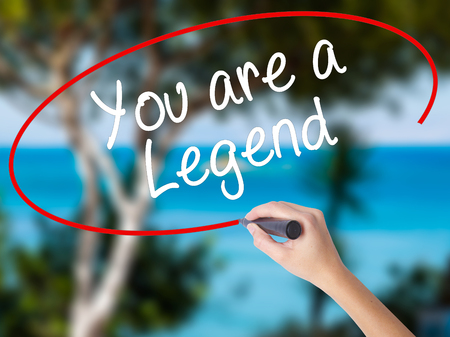 Woman Hand Writing You are a Legend   with black marker on visual screen. Isolated on nature. Business concept. Stock Photo