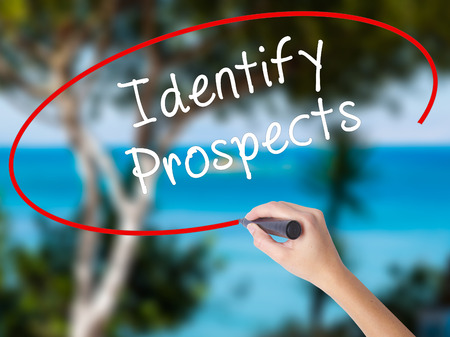 Woman Hand Writing Identify Prospects with black marker on visual screen. Isolated on nature. Business concept. Stock Photo