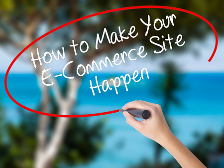 Woman Hand Writing How to Make Your E-Commerce Site Happen with black marker on visual screen. Isolated on nature. Business concept. Stock Photo