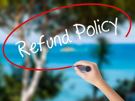 Woman Hand Writing Refund Policy with black marker on visual screen. Isolated on nature. Business concept. Stock Photo