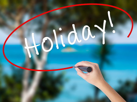 Woman Hand Writing Holiday! with black marker on visual screen. Isolated on nature. Business concept. Stock Photo