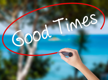 Woman Hand Writing Good Times with black marker on visual screen. Isolated on nature. Business concept. Stock Photo