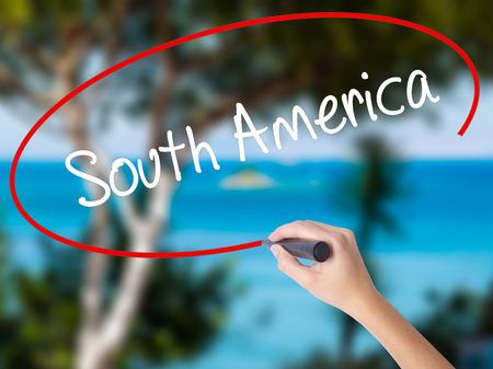 Mano de mujer escribiendo América del sur con marcador negro en la pantalla visual. Aislado en la naturaleza. Concepto de negocio. Foto de stock
