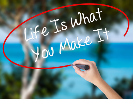 leadership potential: Woman Hand Writing Life Is What You Make It with black marker on visual screen. Isolated on nature. Business concept. Stock Photo Stock Photo