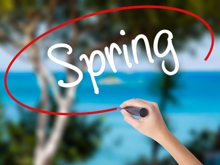 eastertime: Woman Hand Writing Spring with black marker on visual screen. Isolated on nature. Business concept. Stock Photo