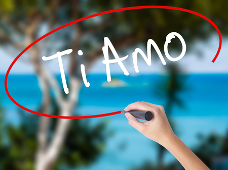Woman Hand Writing Ti Amo (I Love You In Italian) with black marker on visual screen. Isolated on nature. Business concept. Stock  Photo