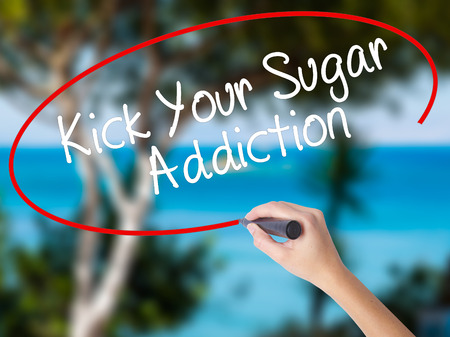 Woman Hand Writing Kick Your Sugar Addiction with black marker on visual screen. Isolated on nature. Business concept. Stock Photo