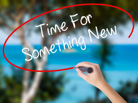 Woman Hand Writing Time For Something New with black marker on visual screen. Isolated on nature. Business concept. Stock Photo Stock Photo