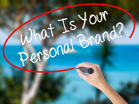 Woman Hand Writing What Is Your Personal Brand? with black marker on visual screen. Isolated on nature. Business concept. Stock Photo