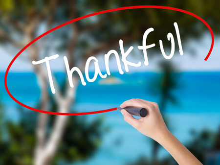 Woman Hand Writing Thankful  with black marker on visual screen. Isolated on nature. Business concept. Stock Photo Stock Photo