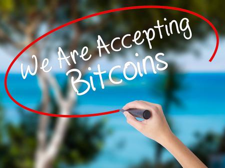 Écriture d'une main de femme, nous acceptons les Bitcoins avec un marqueur noir sur l'écran visuel. Isolé sur la nature. Concept d'affaires Photo en stock