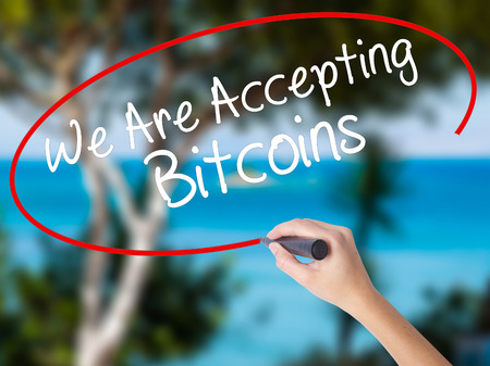 Woman Hand Writing We Are Accepting Bitcoins with black marker on visual screen. Isolated on nature. Business concept. Stock Photo Stock Photo