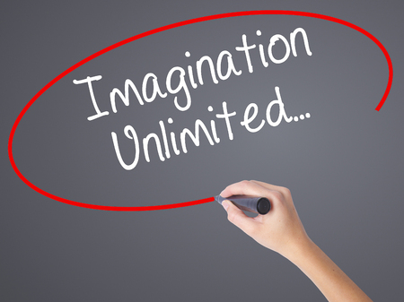 Woman Hand Writing Imagination Unlimited... with black marker on visual screen. Isolated on grey. Business concept. Stock Photo