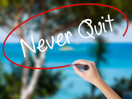 Woman Hand Writing Never Quit with black marker on visual screen. Isolated on nature. Business concept. Stock  Photo