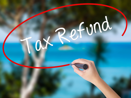 Woman Hand Writing Tax Refund with black marker on visual screen. Isolated on nature. Business concept. Stock Photo